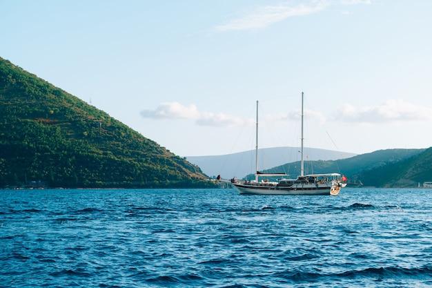 Een groot houten jacht met twee masten vaart op de baai van kotor