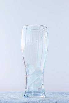Een groot leeg bierglas met ijs staat op een witte achtergrond.