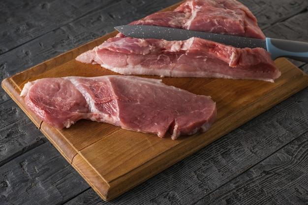 Een groot mes snijdt steaks van een groot stuk varkensvlees op een snijplank. ingrediënten voor het koken van vleesgerechten.