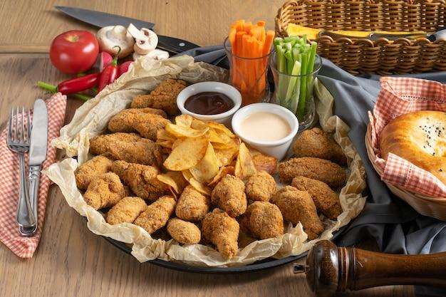 Een groot plateau van gepaneerde kippenvleugels met chips, sauzen en groenten