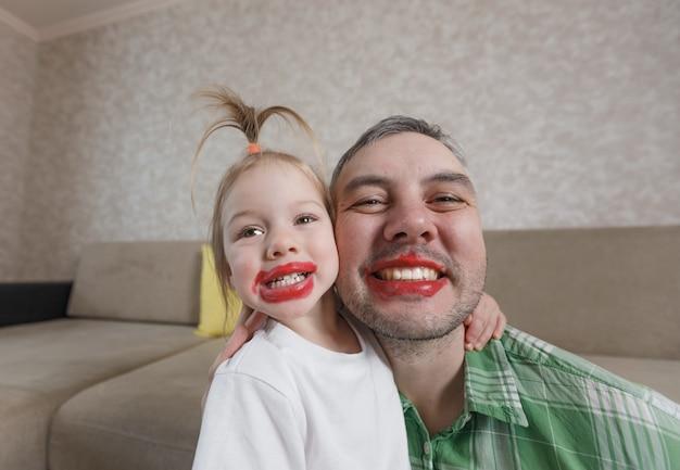 Een groot portret van een vader en dochter met felgekleurde lippen