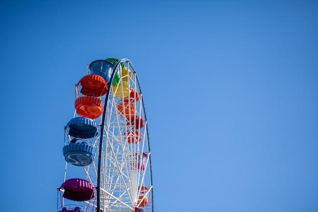 Een groot reuzenrad tegen een blauwe hemel. kraampjes met mensen gaan omhoog. er is een plaats voor de tekst. concept: entertainment tijdens zomervakanties, vakanties met kinderen in het weekend, ride on rides.