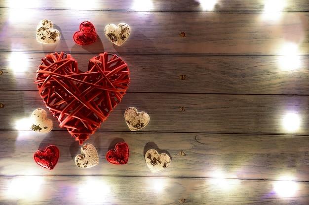 Een groot rood rieten decoratief hart aan de linkerkant en kleine hartjes eromheen. er zijn gloeiende lichten rond het frame. aan de rechterkant is er een plaats voor een inscriptie voor verschillende feestdagen.
