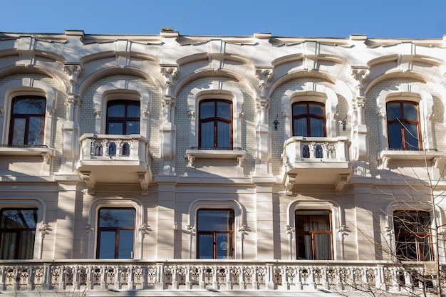 Een groot stenen gebouw met veel ramen. oud klassiek architectuurhuis met veel boogramen en balkons. mooie paleisvoorgevel