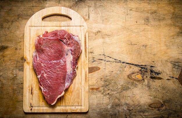 Een groot stuk rauw vers vlees op snijplank. op een houten tafel. vrije ruimte voor tekst. bovenaanzicht