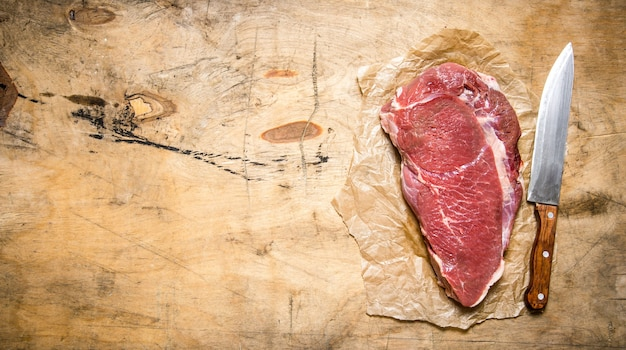 Een groot stuk rauw vlees met een slagersmes op het papier.