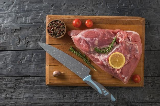 Een groot stuk varkensvlees, een mes, tomaten en knoflook op een snijplank. ingrediënten voor het koken van vleesgerechten. het uitzicht vanaf de top.