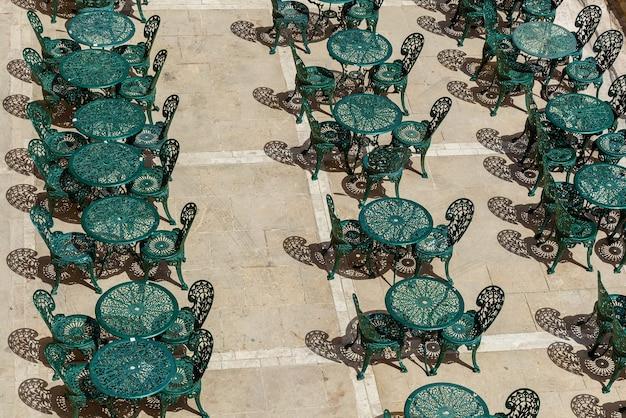 Een groot terras van een openluchtcafé met groene metalen tafels en stoelen met prachtige patronen.