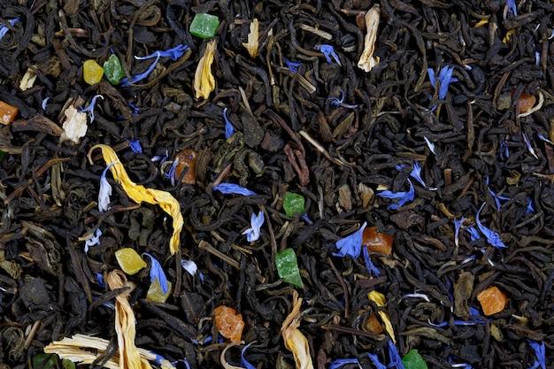 Een groot vel groene thee, korenbloemblaadjes, zonnebloemblaadjes, kleurrijk gekonfijt fruit.