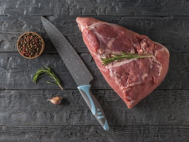 Een groot vleesmes en een groot stuk varkensvlees op een houten tafel. ingrediënten voor het koken van vleesgerechten. het uitzicht vanaf de top.