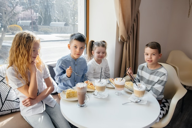 Een groot vriendelijk gezelschap van kinderen viert de vakantie in een café met een heerlijk toetje.
