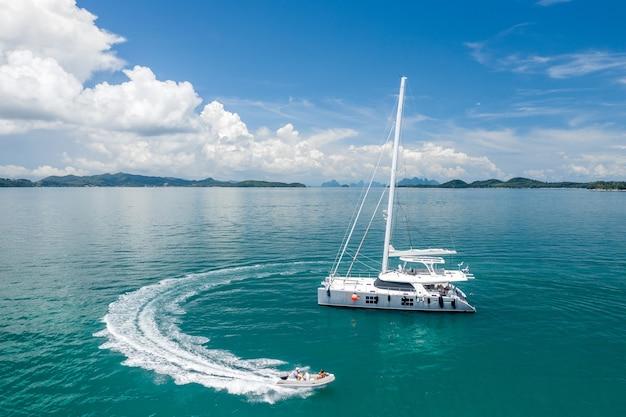 Een groot wit zeiljacht en een motorboot met mensen.