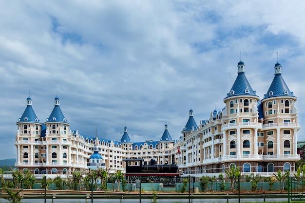 Een groot woongebouw met veel balkons op de achtergrond van een bewolkte blauwe hemel.