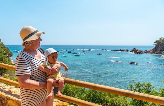 Een grootmoeder en kleinzoon die plezier hebben in de zomer in cala canyet naast de stad tossa de mar. girona, costa brava in de middellandse zee