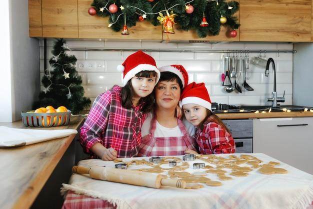 Een grootmoeder en twee kleindochters in rode hoeden omhelzen elkaar in de keuken aan de vooravond van kerstmis. alledaagse levensstijl in het interieur van het echte leven