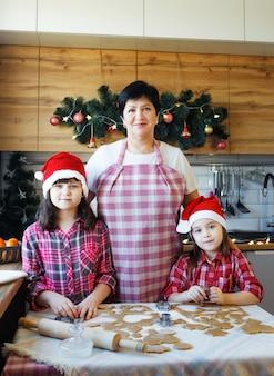 Een grootmoeder en twee kleindochters in rode mutsen bereiden in de aanloop naar kerstmis koekjes in de keuken. alledaagse levensstijl in het interieur van het echte leven