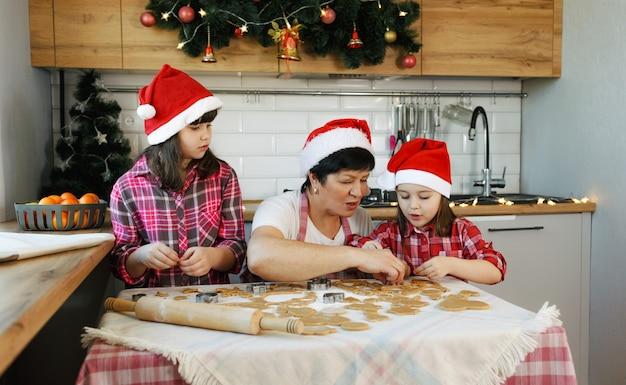 Een grootmoeder en twee kleindochters met rode hoeden bereiden in de keuken in de aanloop naar kerstmis koekjes. alledaagse levensstijl in het interieur van het echte leven