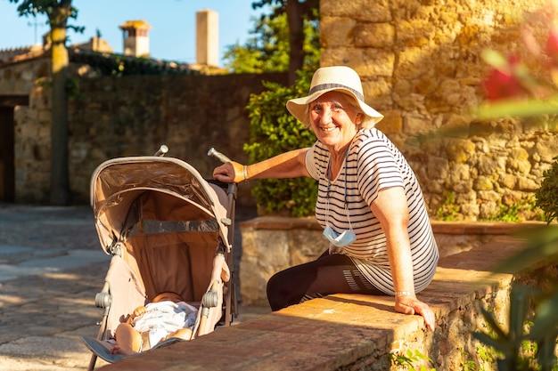 Een grootmoeder met de kleinzoon in het middeleeuwse dorp pals, straten van het historische centrum bij zonsondergang, girona aan de costa brava van catalonië in de middellandse zee