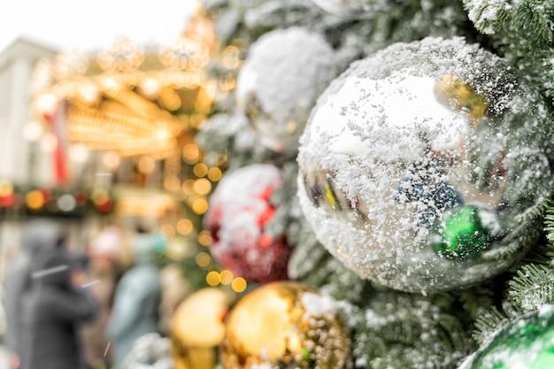 Een grote bal op de sneeuwwinden van een kerstboom.