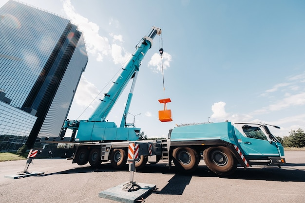 Een grote blauwe autolaadkraan staat klaar voor gebruik op een terrein nabij een groot modern gebouw.