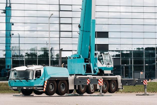 Een grote blauwe vrachtwagenkraan staat klaar om te werken op hydraulische steunen op een platform naast een groot modern gebouw.
