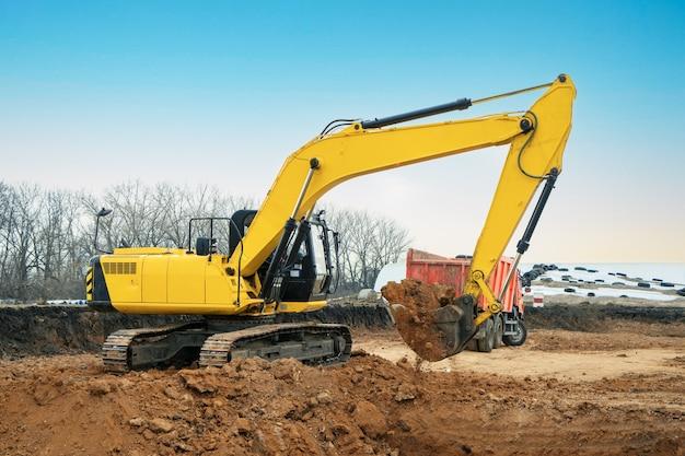 Een grote bouwgraafmachine van gele kleur op de bouwplaats in een steengroeve om te ontginnen. industrieel imago.