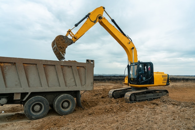 Een grote bouwgraafmachine van gele kleur op de bouwplaats in een steengroeve om te ontginnen