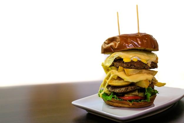 Een grote dubbele hamburger op porseleinen bord en witte achtergrond