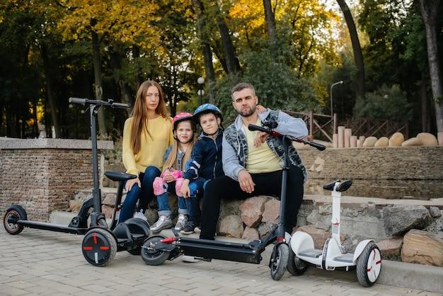 Een grote en gelukkige familie rijdt segways en elektrische scooters in het park op een warme herfstdag tijdens zonsondergang. familievakantie in het park.