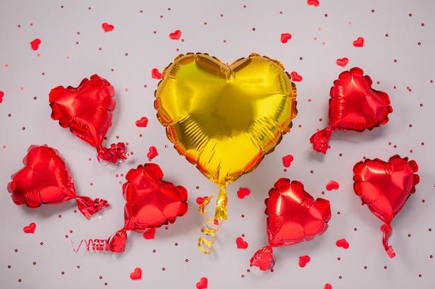 Een grote gele en vele kleine rode luchtballonnen van hartvormige folie. liefde concept. valentijnsdag