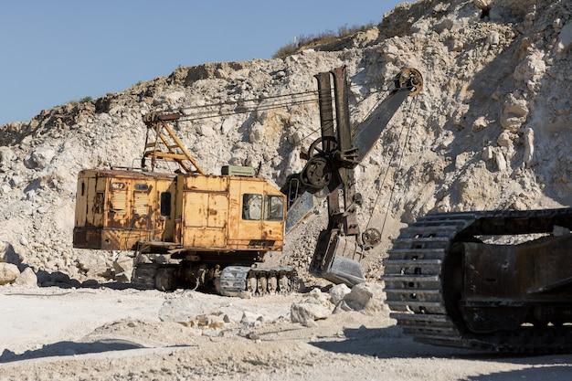 Een grote gele rupsgraafmachine is mijnbouwsteen in een steengroeve.