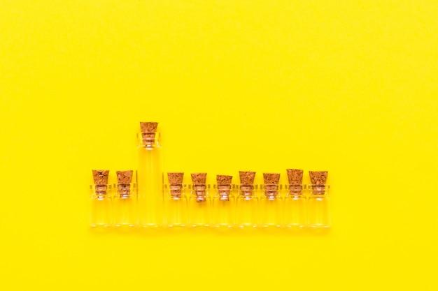 Een grote glazen transparante lege fles met kurken op een rij met dezelfde kleintjes op een gele achtergrond. bovenaanzicht