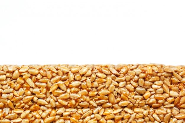 Een grote gouden tegel met zonnebloempitten, een reep zoete melasse. kozinaki nuttige en smakelijke zoetigheden van het oosten