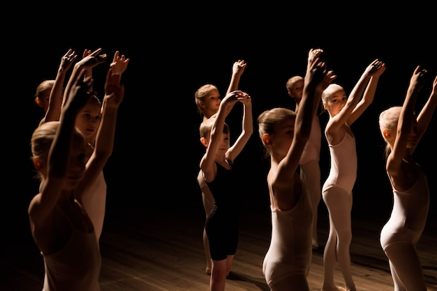 Een grote groep kinderen die het ballet repeteren en dansen