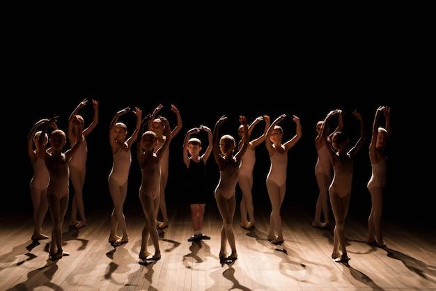 Een grote groep kinderen die het ballet repeteren en dansen.