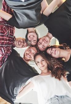 Een grote groep lachende vrienden knuffelen samen.