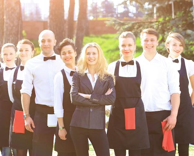 Een grote groep vriendelijke obers en serveersters die in een rij achter elkaar staan