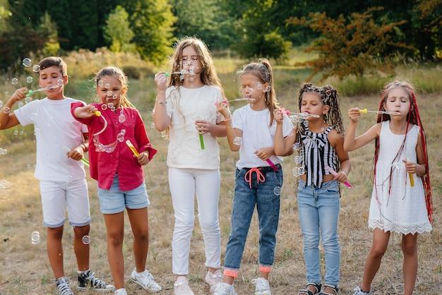 Een grote groep vrolijke kinderen speelt in het park en blaast zeepbellen op. games in een kinderkamp.