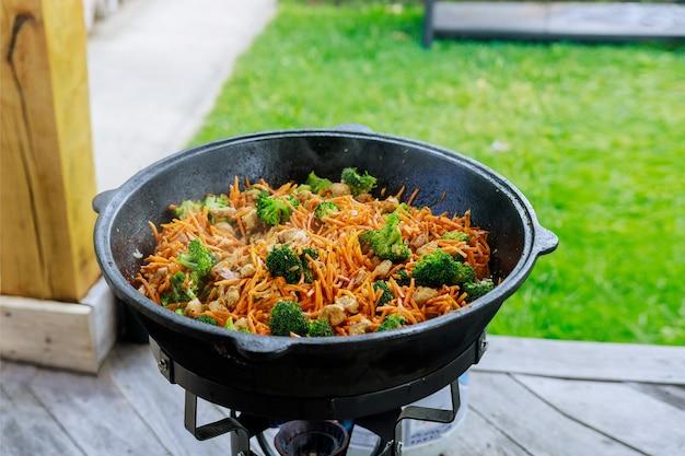 Een grote ketel met een gekookte gezonde groente voor een feestje buiten.