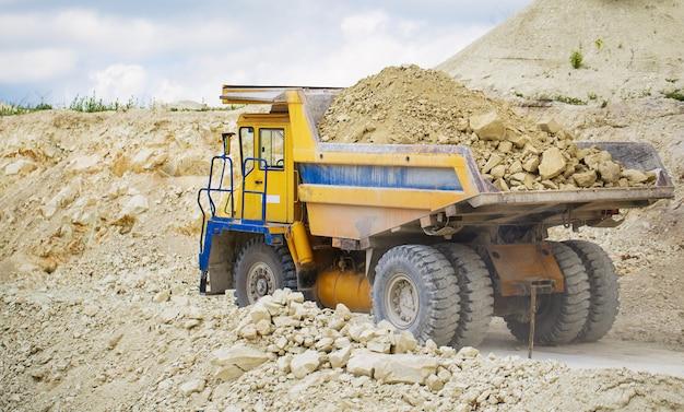 Een grote kiepwagen met steen beladen