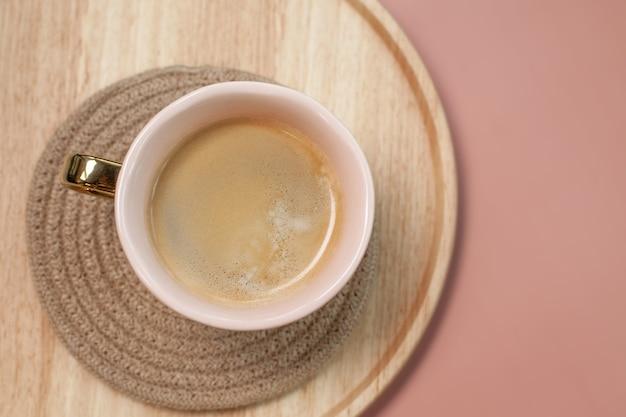 Een grote kop hete koffie. bovenaanzicht. houten dienblad. roze achtergrond