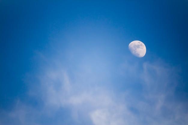 Een grote maan in de middag tegen een blauwe lucht met wolken