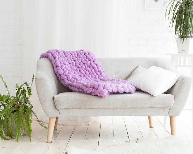 Een grote merino lila plaid deken ligt op de bank.