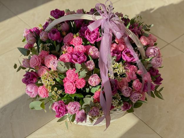 Een grote mooie mand met felroze bloemen met tulpen, rozen en eucalyptus. achtergrondafbeelding met bloemen onder het zonlicht