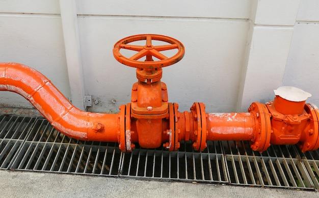 Een grote oranjekleurige hoofdleiding van de waterlevering met een plugkraanklep tegen een concrete muur.