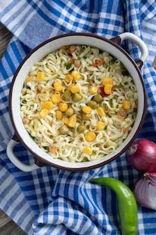 Een grote pan noedels met groenten op tafellaken