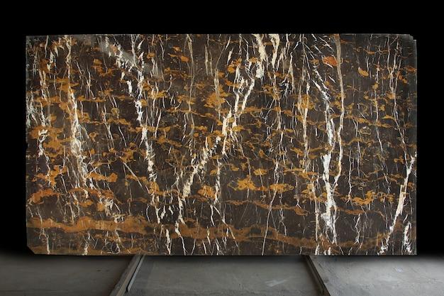 Een grote plaat van gepolijste natuursteen. bruin marmer met gele en witte strepen genaamd black and gold.