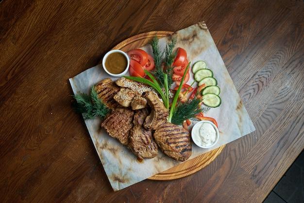 Een grote portie gegrilde kebab. varkenshaas, biefstuk gekookt in een barbecue met verschillende sauzen en verse groenten. shashlic. bovenaanzicht voedsel vlees.