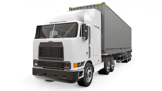 Een grote retro witte vrachtwagen met een slaapgedeelte en een aerodynamische uitbreiding draagt een aanhangwagen met een zeecontainer