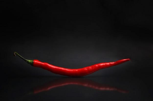 Een grote rode chili geïsoleerd van een zwarte achtergrond
